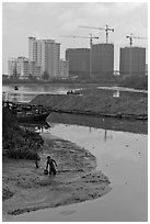 Man wading in mud, with background of towers in construction, Phu My Hung, district 7. Ho Chi Minh City, Vietnam (black and white)