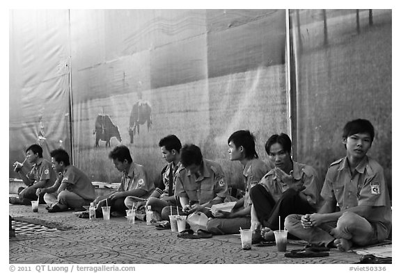 Uniformed students sitting in front of backdrops depicting traditional landscapes. Ho Chi Minh City, Vietnam (black and white)