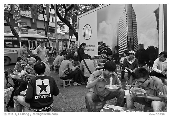 Uniformed students eating breakfast in front of backdrop depicting high rise in construction. Ho Chi Minh City, Vietnam (black and white)
