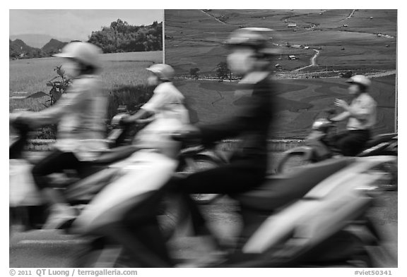 Motorbike riders speeding in front of backdrops depicting traditional landscapes. Ho Chi Minh City, Vietnam (black and white)