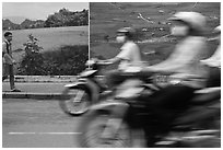 Man walking and motorbike riders blured in front of backdrops depicting traditional landscapes. Ho Chi Minh City, Vietnam (black and white)
