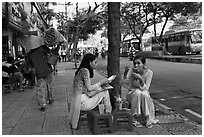 Women elegantly dressed in ao dai eating on the street. Ho Chi Minh City, Vietnam ( black and white)