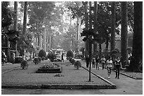 People strolling in alley below tall trees, Cong Vien Van Hoa Park. Ho Chi Minh City, Vietnam ( black and white)
