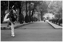 Woman plays badminton using feet (footbag), Cong Vien Van Hoa Park. Ho Chi Minh City, Vietnam (black and white)