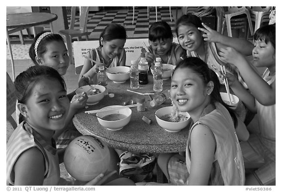 Girls sports team eating, Van Hoa Park. Ho Chi Minh City, Vietnam (black and white)