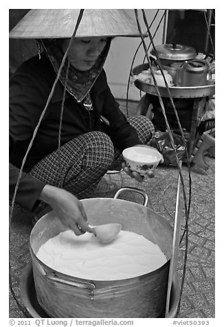 Woman serving a bowl of soft tofu. Ho Chi Minh City, Vietnam (black and white)
