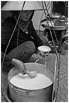 Woman serving a bowl of soft tofu. Ho Chi Minh City, Vietnam ( black and white)