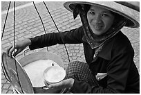 Woman smiling while handling bowl of soft tofu. Ho Chi Minh City, Vietnam ( black and white)