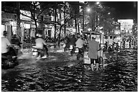 Traffic passes man pushing food cart on flooded street at night. Ho Chi Minh City, Vietnam (black and white)