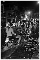 Couple riding motorcycle on flooded street at night. Ho Chi Minh City, Vietnam (black and white)