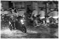 Man riding motorbike on flooded street seen against riders going in opposite direction. Ho Chi Minh City, Vietnam (black and white)