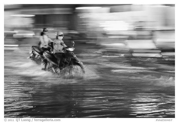 Motorcycle riders, water splashes, and streaks of light. Ho Chi Minh City, Vietnam (black and white)