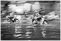 Motion-blured exposure of riders on flooded street at night. Ho Chi Minh City, Vietnam (black and white)
