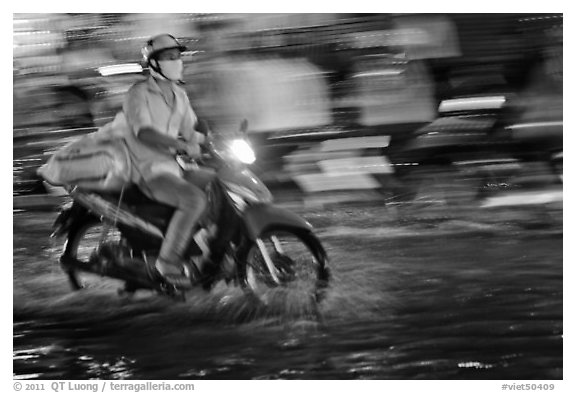 Motorcycle rider photographed with panning motion at night. Ho Chi Minh City, Vietnam (black and white)