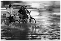 Bicyle and motorbike riders on monsoon-flooded street. Ho Chi Minh City, Vietnam (black and white)