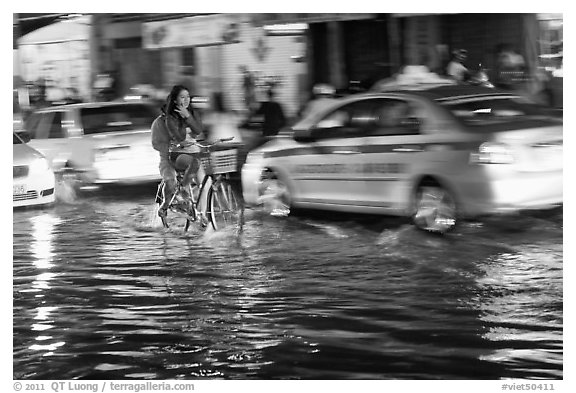 Women riding a bicycle on a flooded street at night. Ho Chi Minh City, Vietnam (black and white)
