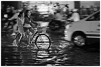 Women sharing a bicycle ride at night on a water-filled street. Ho Chi Minh City, Vietnam (black and white)
