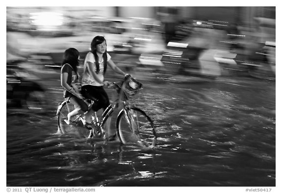Girls sharing night bicycle ride through water of flooded street. Ho Chi Minh City, Vietnam (black and white)
