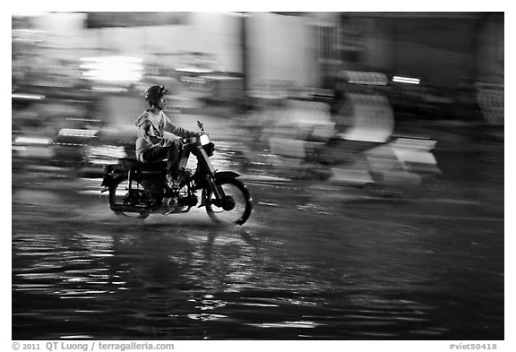 Motorcyclist speeding on wet street at night, with streaks giving sense of motion. Ho Chi Minh City, Vietnam (black and white)