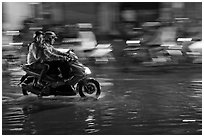 Couple sharing fast night ride on wet street. Ho Chi Minh City, Vietnam (black and white)