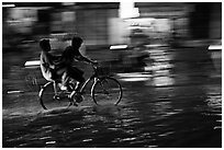 Men sharing bicycle ride at night on wet street. Ho Chi Minh City, Vietnam (black and white)