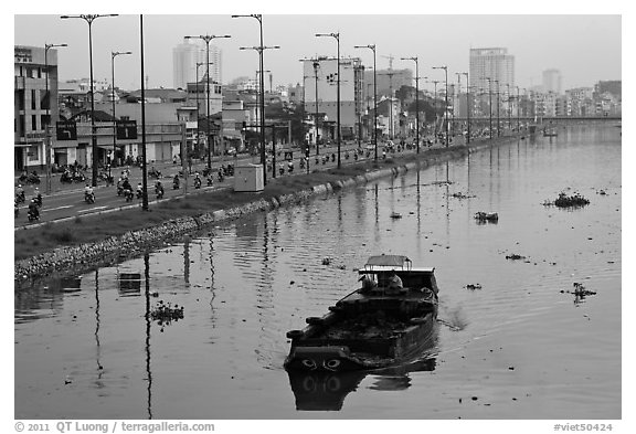 Barge with traditional painted eyes on Saigon Arroyau with backdrop of expressway traffic. Cholon, Ho Chi Minh City, Vietnam (black and white)