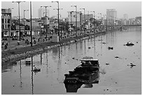 Barge with traditional painted eyes on Saigon Arroyau with backdrop of expressway traffic. Cholon, Ho Chi Minh City, Vietnam ( black and white)