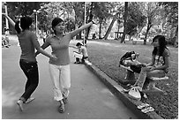 Young women dancing to sound of mobile phone, Tao Dan Park. Ho Chi Minh City, Vietnam ( black and white)