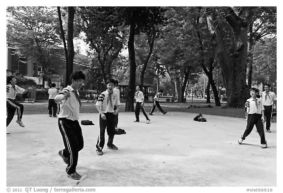 Schoolboys playing a feet badminton game, Cong Vien Van Hoa Park. Ho Chi Minh City, Vietnam (black and white)