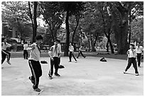 Schoolboys playing a feet badminton game, Cong Vien Van Hoa Park. Ho Chi Minh City, Vietnam ( black and white)