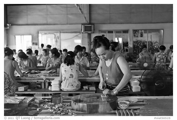 Woman cutting strips of coconut candy in factory. Ben Tre, Vietnam (black and white)