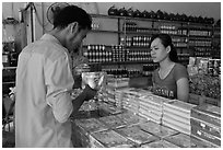 Customer buying box of coconut candy. Ben Tre, Vietnam ( black and white)