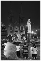 Family in prayer outside Notre-Dame Basilica at night. Ho Chi Minh City, Vietnam ( black and white)