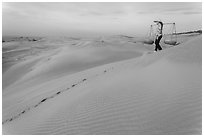 Woman descending sandhill with pannier baskets. Mui Ne, Vietnam (black and white)