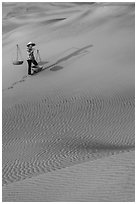 Woman with yoke baskets on sands. Mui Ne, Vietnam ( black and white)