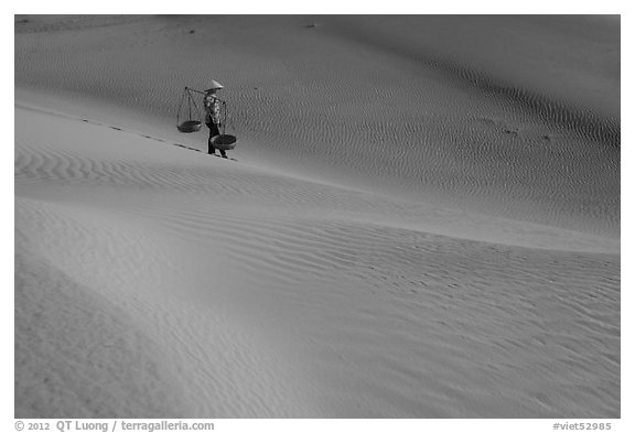 Woman with conical hat and yoke baskets pauses on sand dunes. Mui Ne, Vietnam (black and white)