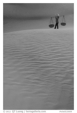 Figure with conical hats and two baskets on sand dunes. Mui Ne, Vietnam (black and white)