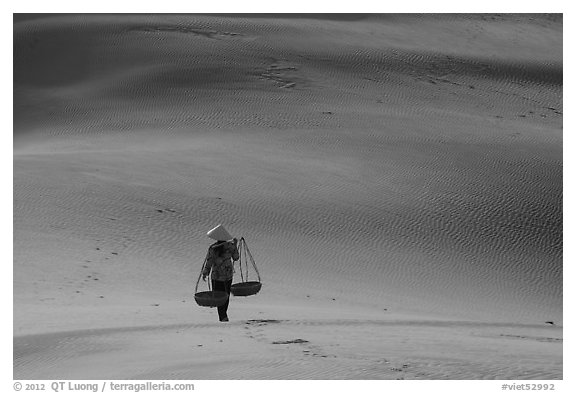 Woman walking on dune field with yoke baskets. Mui Ne, Vietnam (black and white)