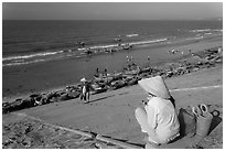 Woman on stairs overlooking beach with fishing boats. Mui Ne, Vietnam (black and white)