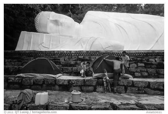 Pilgrims pitch tent below reclining Buddha statue. Ta Cu Mountain, Vietnam (black and white)