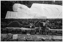 Pilgrims pitch tent below reclining Buddha statue. Ta Cu Mountain, Vietnam ( black and white)