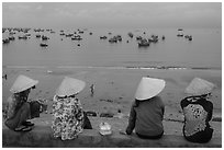 Four women in conical hats watch fishing activity from high above fishing village. Mui Ne, Vietnam (black and white)