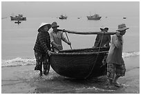Fishermen carry round woven boat to shore. Mui Ne, Vietnam (black and white)