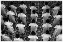 Worshippers dressed in white stand in rows in Cao Dai temple. Tay Ninh, Vietnam ( black and white)