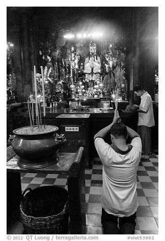 Worshippers inside Jade Emperor Pagoda. Ho Chi Minh City, Vietnam (black and white)