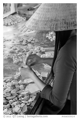 Woman wearing conical hat wrapping coconut candy, Phoenix Island. My Tho, Vietnam (black and white)