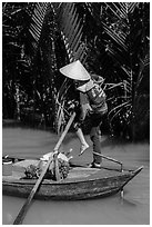Woman standing in canoe on jungle canal, Phoenix Island. My Tho, Vietnam ( black and white)