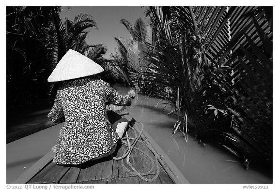 Woman rowing boat in canal lined up with vegetation, Phoenix Island. My Tho, Vietnam (black and white)