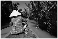 Woman rowing boat in canal lined up with vegetation, Phoenix Island. My Tho, Vietnam ( black and white)