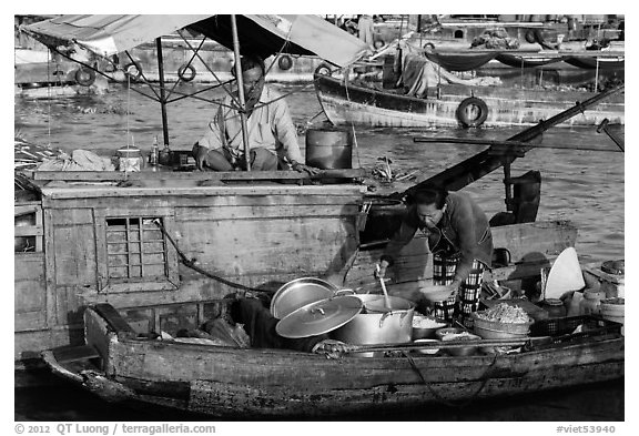 Woman serving food across boats, Cai Rang floating market. Can Tho, Vietnam (black and white)